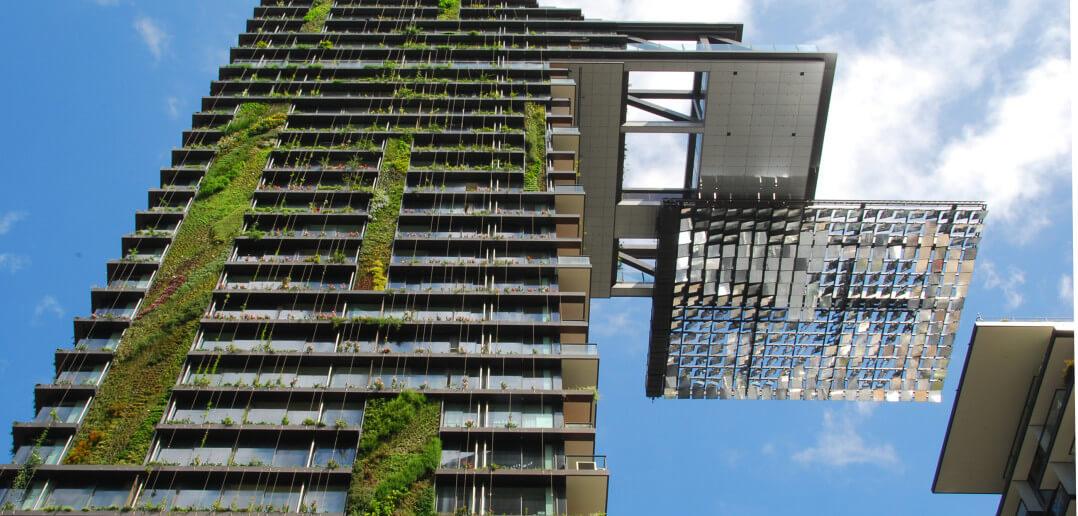 Ein Foto von einem Hochhaus von unten aufgenommen. Ähnlich wie bei bosco verticale wachsen an der Fassade Pflanzen.