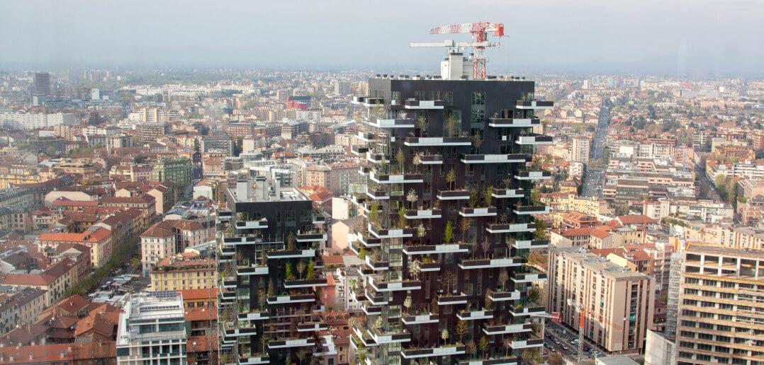Das Foto zeigt zwei Hochhäuser. An den Fassaden des bosco verticale wachsen viele Bäume und Büsche auf Terrassen und Balkonen.