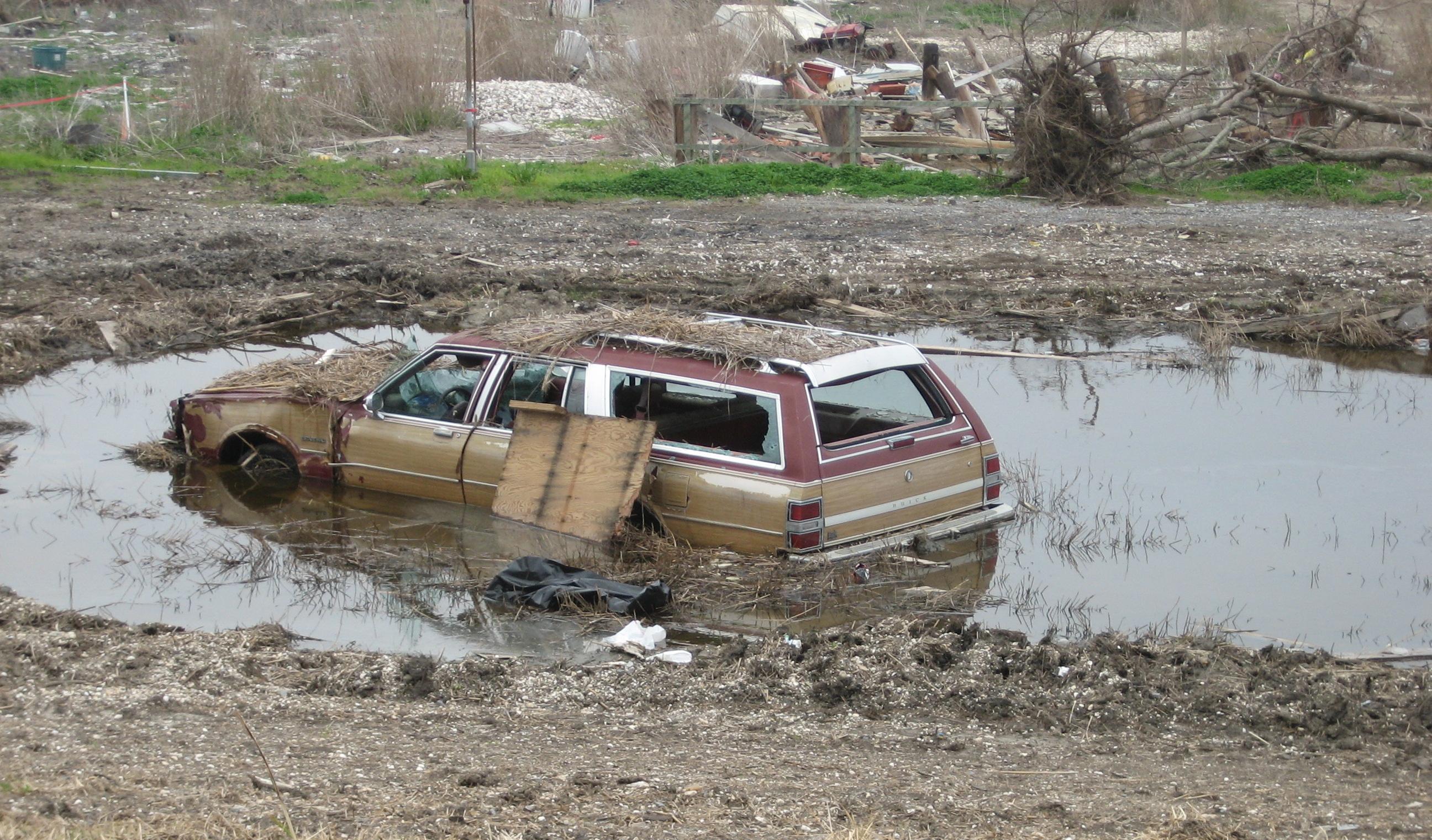 Das Foto zeigt ein Auto in einer großen Wasserlache nach dem Hurrikan Katrina in New Orleans. Überschwemmungen fordern Städte und ihre Resilienz heraus.